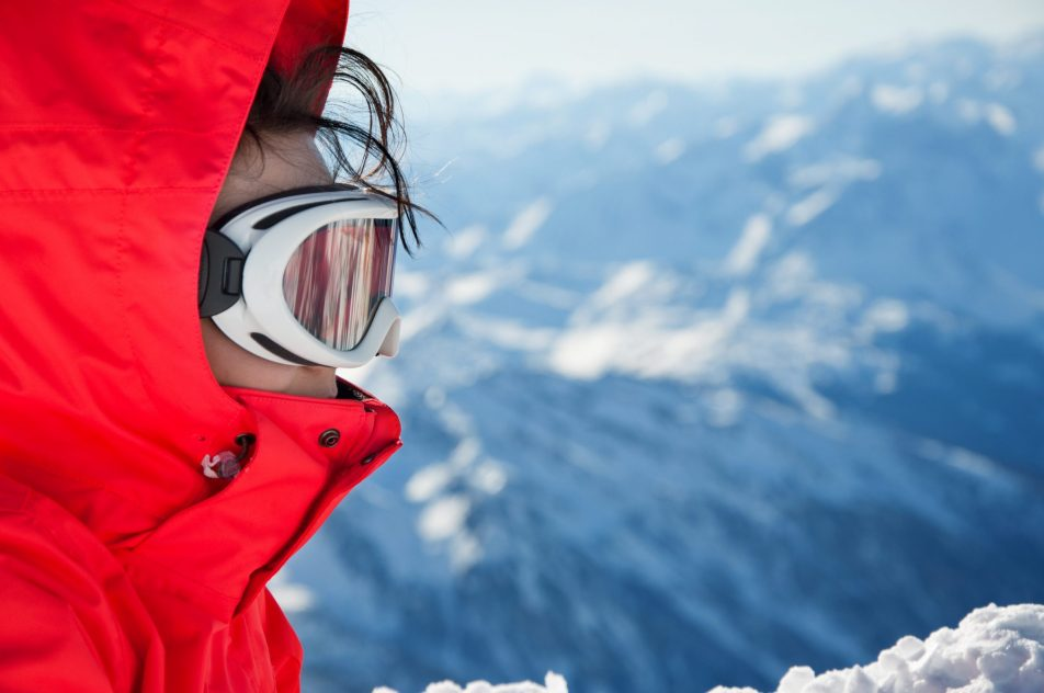 Close-up of skiing girl with goggles, on mountains background