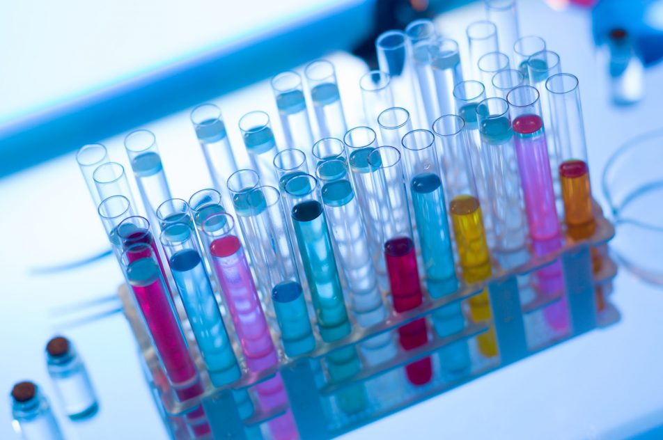close-up of rack of medical tubes filled with colorful fluids placed on table in a laboratory