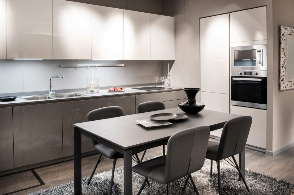 Monochrome grey and white kitchen interior with built in cabinets and appliances and a center dining table and chairs with vases