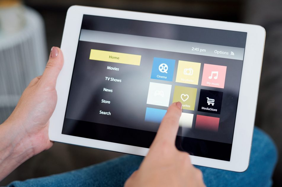 Young female touching heart icon on touchpad display while choosing something to watch